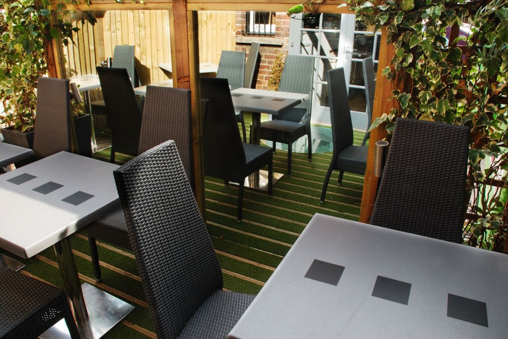 Mirrored restaurant patio with faux-grass decking